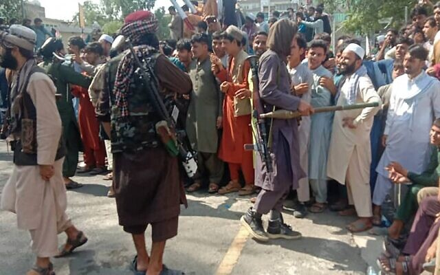 Taliban fighters and local people are pictured along the street in Jalalabad province on August 15, 2021. (AFP)