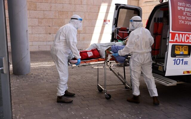 Medics with Magen David Adom transfer a coronavirus patient to the Hadassah Ein Kerem Hospital in Jerusalem, due to full capacity in other hospitals, following a sharp increase in the number of coronavirus infections in Israel, on August 15, 2021. (Menahem KAHANA / AFP)