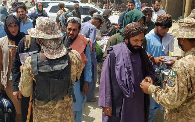 Pakistani soldiers check the documents of stranded Afghan nationals wanting to return to Afghanistan at the Pakistan-Afghanistan border crossing point in Chaman, on August 15, 2021. (AFP)
