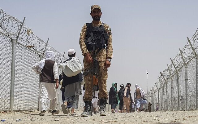 A Pakistani soldier stands guard as stranded Afghan nationals return to Afghanistan at the Pakistan-Afghanistan border crossing point in Chaman on August 15, 2021, after the Taliban took control of the Afghan border town in a rapid offensive across the country. (AFP)