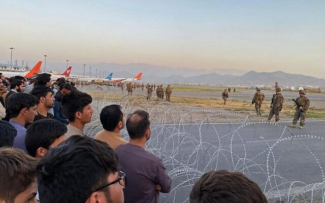 Afghans (L) crowd at the airport as US soldiers (R) stand guard in Kabul on August 16, 2021. (Shakib Rahmani / AFP)