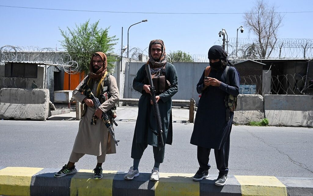 Taliban fighters stand guard along a street in Kabul on August 16, 2021, after a stunningly swift end to Afghanistan's 20-year war, as thousands of people mobbed the city's airport trying to flee the group's feared hardline brand of Islamist rule. (Wakil Kohsar / AFP)