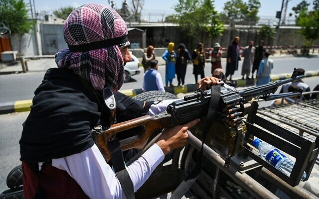 A Taliban fighter mans a machinegun on top of a vehicle as they patrol along a street in Kabul on August 16, 2021, after a stunningly swift end to Afghanistan's 20-year war, as thousands of people mobbed the city's airport trying to flee the group's feared hardline brand of Islamist rule. (Wakil Kohsar / AFP)