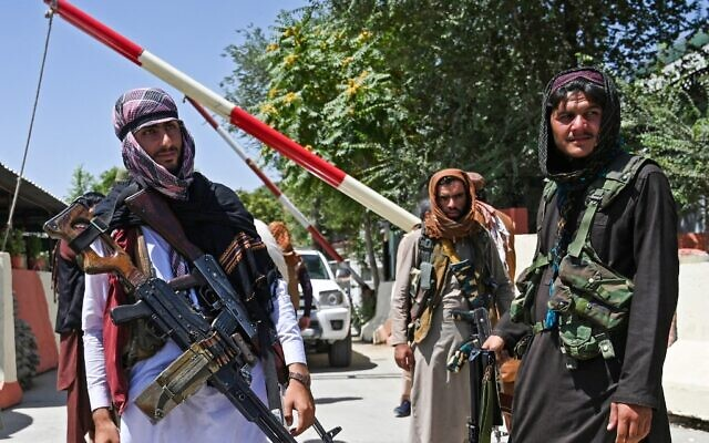 Taliban fighters stand guard along a roadside near the Zanbaq Square in Kabul on August 16, 2021, after a stunningly swift end to Afghanistan's 20-year war, as thousands of people mobbed the city's airport trying to flee the group's feared hardline brand of Islamist rule. (Wakil Kohsar / AFP)