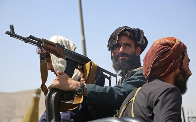 Taliban fighters stand guard in a vehicle along the roadside in Kabul on August 16, 2021 (AFP)