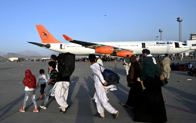 Afghan families walk by the aircrafts at the Kabul airport in Kabul on August 16, 2021, after a stunningly swift end to Afghanistan's 20-year war, as thousands of people mobbed the city's airport trying to flee the group's feared hardline brand of Islamist rule. (Wakil Kohsar / AFP)