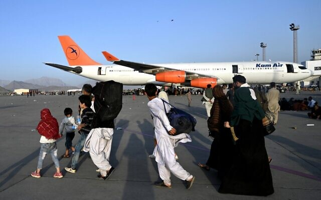 Afghan families walk by planes at the airport in Kabul on August 16, 2021. (Wakil Kohsar/AFP)