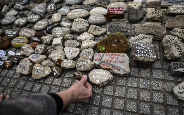 """A woman places a stone with the name of a relative outside the Casa Rosada government house during the """"march of the stones"""" in homage to COVID-19 victims, in Buenos Aires, Argentina, on August 16, 2021. (Ronaldo Schmeidt/AFP)"""