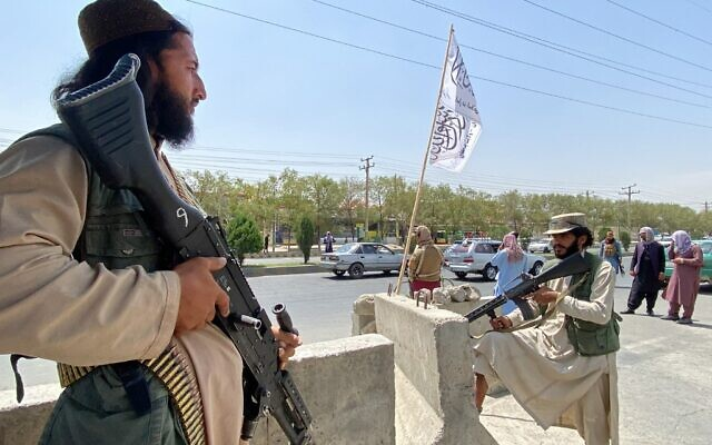 Taliban fighters stand guard at an entrance gate outside the Interior Ministry in Kabul, on August 17, 2021. (Javed Tanveer/AFP)