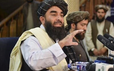 Taliban spokesperson Zabihullah Mujahid (L) gestures as he speaks during the first press conference in Kabul on August 17, 2021, following the Taliban's stunning takeover of Afghanistan. (Hoshang Hashimi / AFP)