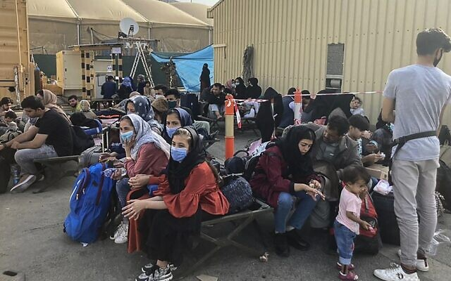 People wait to be evacuated from Afghanistan at the airport in Kabul on August 18, 2021 following the Taliban stunning takeover of the country. (AFP)