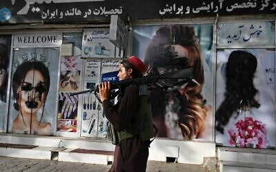 A Taliban fighter walks past a beauty salon with images of women defaced using spray paint in Shar-e-Naw in Kabul on August 18, 2021. (Wakil KOHSAR / AFP)