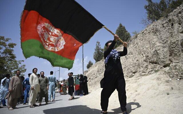 An Afghan waves the national flag in Kabul on August 19, 2021. (WAKIL KOHSAR / AFP)