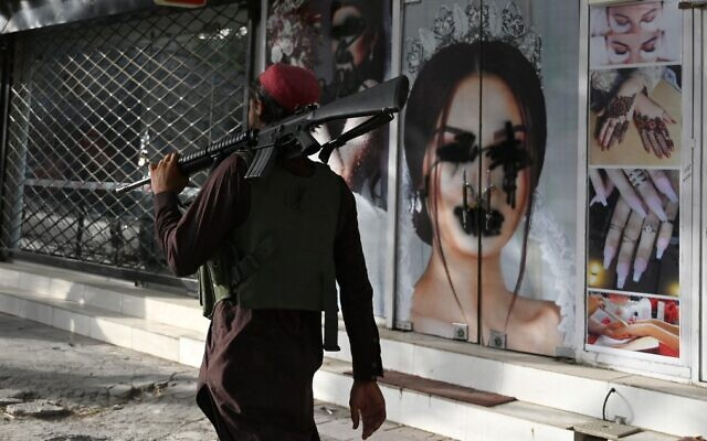 A Taliban fighter walks past a beauty salon with defaced images of women in Shar-e-Naw, Kabul, August 18, 2021. (Wakil Kohsar/AFP)