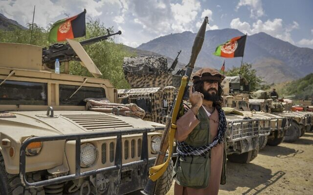 An armed Afghan man supporting the Afghan security forces against the Taliban stands next to humvees at Parakh area in Bazarak, Panjshir province, on August 19, 2021. (Ahmad Sahel Arman/AFP)