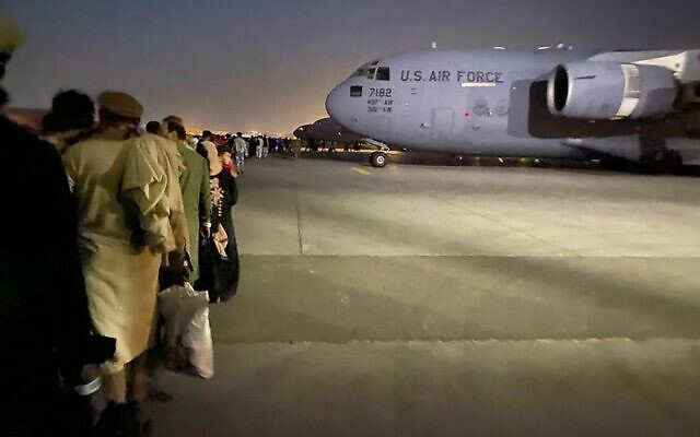 Afghans line up to board a US military aircraft to leave Afghanistan, at the military airport in Kabul, on August 19, 2021, after the Taliban's takeover of Afghanistan. (Shakib Rahmani/AFP)