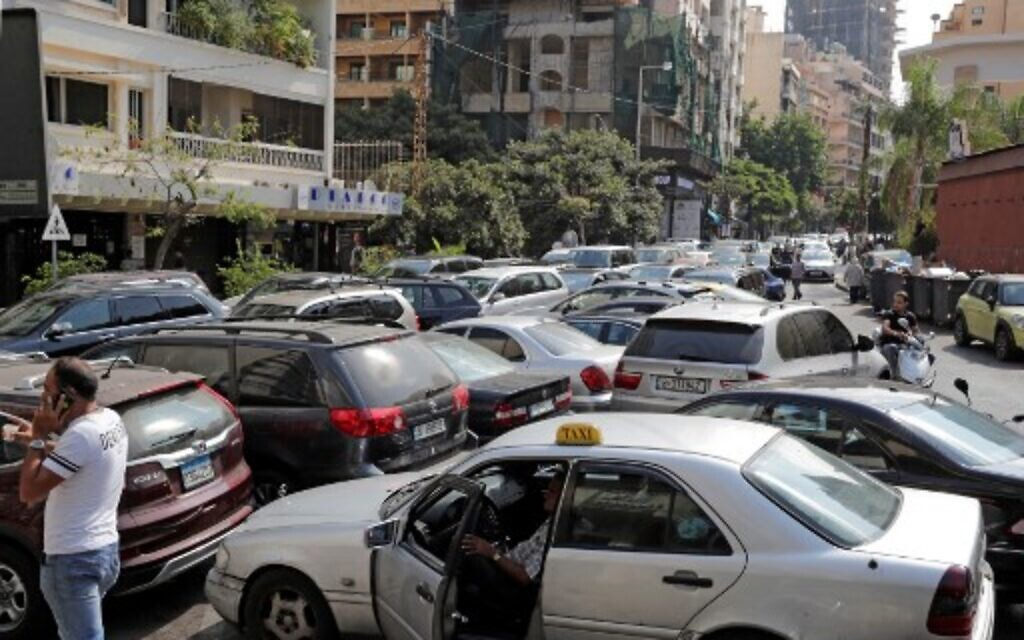 Lebanese wait in a line outside a closed petrol station in Beirut's Hamra district  on August 20, 2021.(Photo by ANWAR AMRO / AFP)