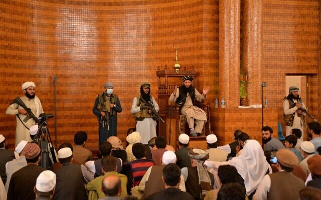 Illustrative: Armed Taliban fighters stand next to an imam during Friday prayers at the Abdul Rahman Mosque in Kabul on August 20, 2021. (Hoshang Hashimi/AFP)