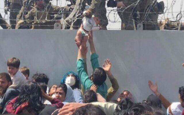 This image made available to AFP on August 20, 2021 by Omar Haidiri, shows a US Marine grabbing an infant over a fence of barbed wire during an evacuation at Hamid Karzai International Airport in Kabul on August 19, 2021.  (Courtesy of Omar Haidiri / AFP)