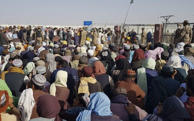 Afghan and Pakistani nationals gather to cross into Afghanistan at the Pakistan-Afghanistan border crossing point in Chaman on August 21, 2021 days after the Taliban stunning takeover of Afghanistan. (Photo by STRINGER / AFP)