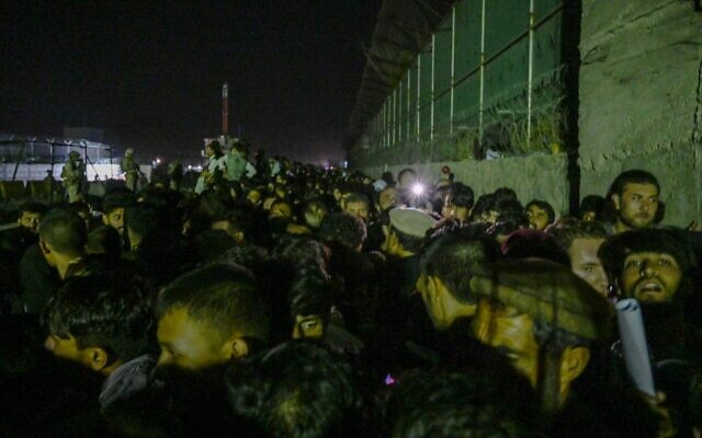 In this picture taken in the late hours on August 22, 2021 Afghans wait outside the foreign military-controlled part of the airport in Kabul, hoping to flee the country following the Taliban's military takeover of Afghanistan. (WAKIL KOHSAR / AFP)