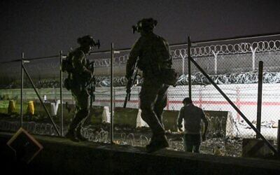 In this picture taken in the late hours on August 22, 2021, British and Canadian soldiers stand guard near a canal as Afghans wait outside the foreign military-controlled part of the airport in Kabul, hoping to flee the country following the Taliban's military takeover of Afghanistan. (Wakil Kohsar/AFP)