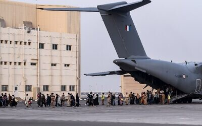 People walk on the tarmac as they disembark from a Airbus A400M military transport aircraft at the French military air base 104 of Al Dhafra, near Abu Dhabi, on August 23, 2021, after being evacuated from Kabul (BERTRAND GUAY / AFP)