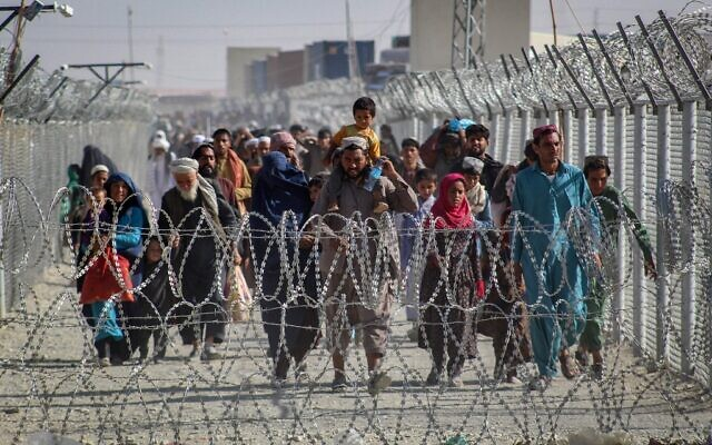 Afghans walk along fences as they arrive in Pakistan through the Pakistan-Afghanistan border crossing point in Chaman on August 24, 2021 following Taliban's military takeover of Afghanistan. (AFP)