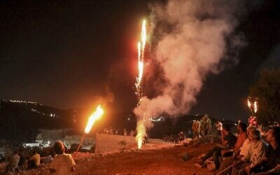 In this file photo taken on August 3, 2021, Palestinians light up flares as they gather for a demonstration against the Israeli outpost of Evyatar in the village of Beita in the West Bank. (JAAFAR ASHTIYEH / AFP)