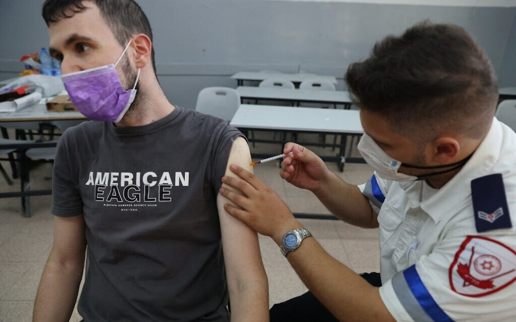 A Magen David Adom paramedic administers a third dose of the Pfizer-BioNTech COVID-19 vaccine to an Israeli man, on August 24, 2021, in the Tel Aviv suburb of Holon. (Ahmad Gharabli/AFP)