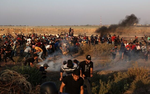 Palestinians run from tear gas fired by Israeli security forces along the border fence, east of Khan Younis in the southern Gaza Strip, on August 25, 2021. (Mahmud Hams/AFP)