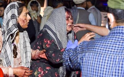 Wounded women arrive at a hospital for treatment after two deadly blasts outside the airport in Kabul on August 26, 2021. (Wakil KOHSAR / AFP)