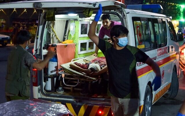 Medical staff bring an injured man to a hospital in an ambulance after two powerful explosions outside the airport in Kabul on August 26, 2021. (Wakil KOHSAR / AFP)
