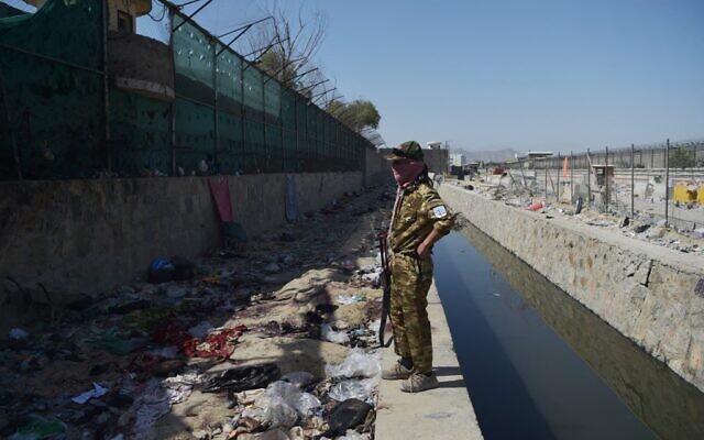 A Taliban fighter stands guard at the site of the August 26 twin suicide bombs, which killed scores of people including 13 US troops, at Kabul airport on August 27, 2021. (WAKIL KOHSAR / AFP)