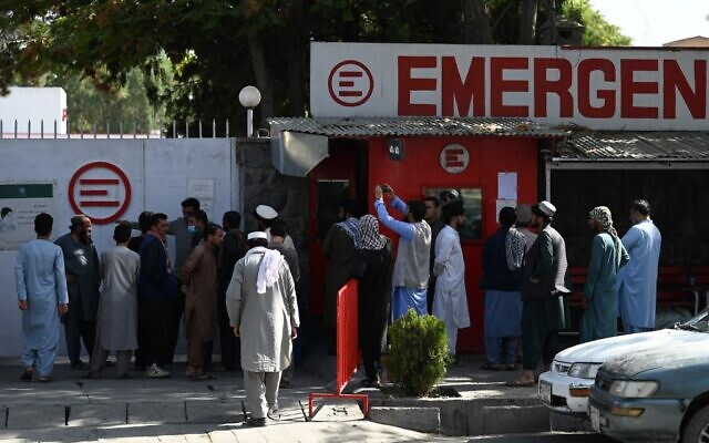 People gather to check on missing relatives a day after a twin suicide bombs attack, which killed scores of people including 13 US troops outside Kabul airport, at a hospital run by Italian NGO Emergency in Kabul, on August 27, 2021. (Photo by Aamir Qureshi/AFP)
