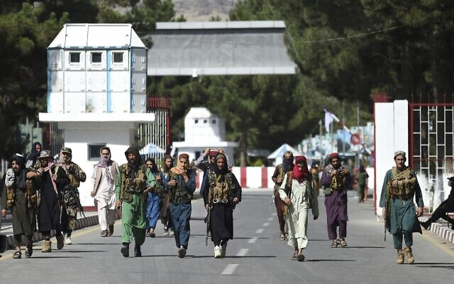 Taliban fighters walk at the main entrance gate of Kabul airport, on August 28, 2021. (Wakil Kohsar/AFP)