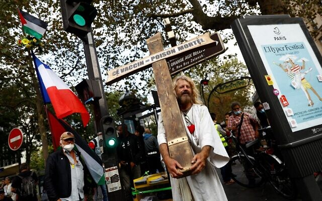 A Frenchman dressed as Jesus holds a cross and a sign reading 'Vaccine = lethal poison' during a rally against the compulsory COVID-19 vaccination for certain workers and the mandatory use of the health pass, near Place du Colonel Fabien in Paris, on August 28, 2021. (Sameer Al-Doumy/AFP)