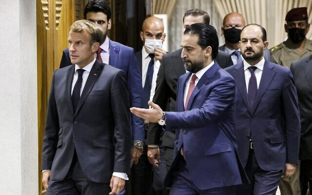 Iraqi Parliament Speaker Muhammad al-Halbousi (R) receives France's President Emmanuel Macron ahead of a meeting at the parliament in the capital Baghdad, on August 28, 2021. (Ludovic MARIN / AFP)