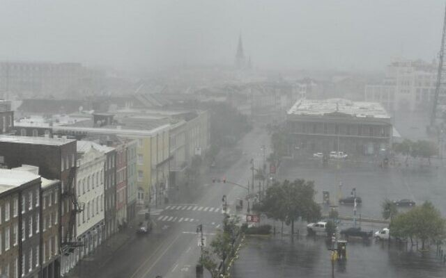 """Rain batters Canal Street in New Orleans, Louisiana on August 29, 2021 after Hurricane Ida made landfall. - Ida made landfall as """"an extremely dangerous"""" Category 4 storm in Louisiana on Sunday, according to the National Hurricane Cente (Photo by Patrick T. FALLON / AFP)"""