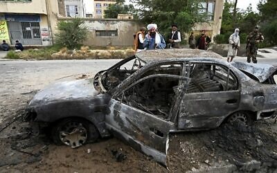 Taliban fighters investigate a damaged car after multiple rockets were fired in Kabul on August 30, 2021.  (Wakil Kohsar / AFP)