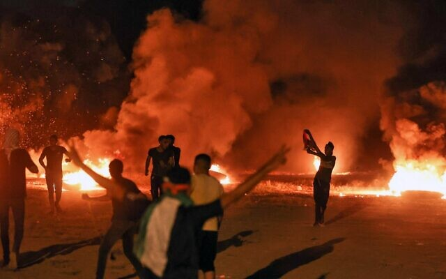 Palestinians burn tires on August 30, 2021 during a protest along the border fence with Israel. (MOHAMMED ABED / AFP)