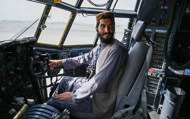 A Taliban fighter sits in the cockpit of an Afghan Air Force aircraft at the airport in Kabul on August 31, 2021 (Wakil KOHSAR / AFP)