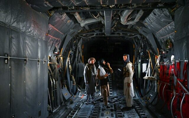 Taliban fighters stand inside an Afghan Air Force aircraft at the airport in Kabul on August 31, 2021 (Wakil KOHSAR / AFP)