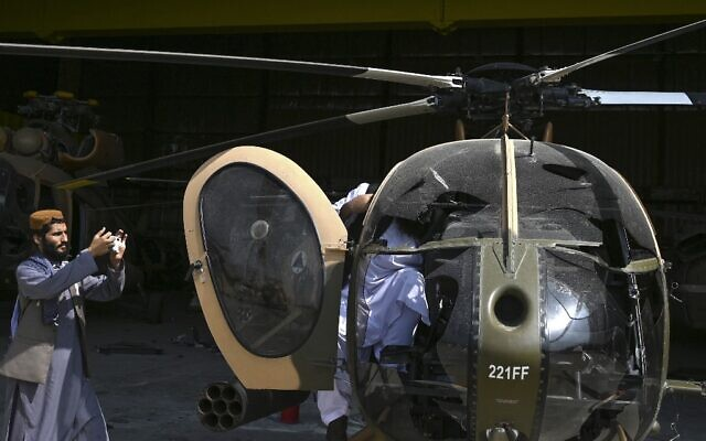 A Taliban fighter takes a picture of a damaged Afghan Air Force's MD 530 helicopter with his mobile phone near the hangar at the airport in Kabul on August 31, 2021 (WAKIL KOHSAR / AFP)