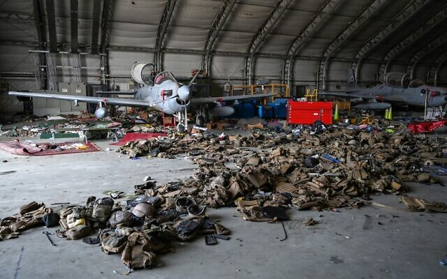 Afghan Air Force's A-29 attack aircrafts are pictured as armoured vests are lying on the ground inside a hangar at the airport in Kabul on August 31, 2021. (WAKIL KOHSAR / AFP)