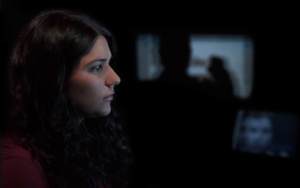 Maia Levy watches footage from the Israeli-Palestinian conflict in the documentary 'The Viewing Booth.' (Courtesy of Atzmor Productions/ via JTA)