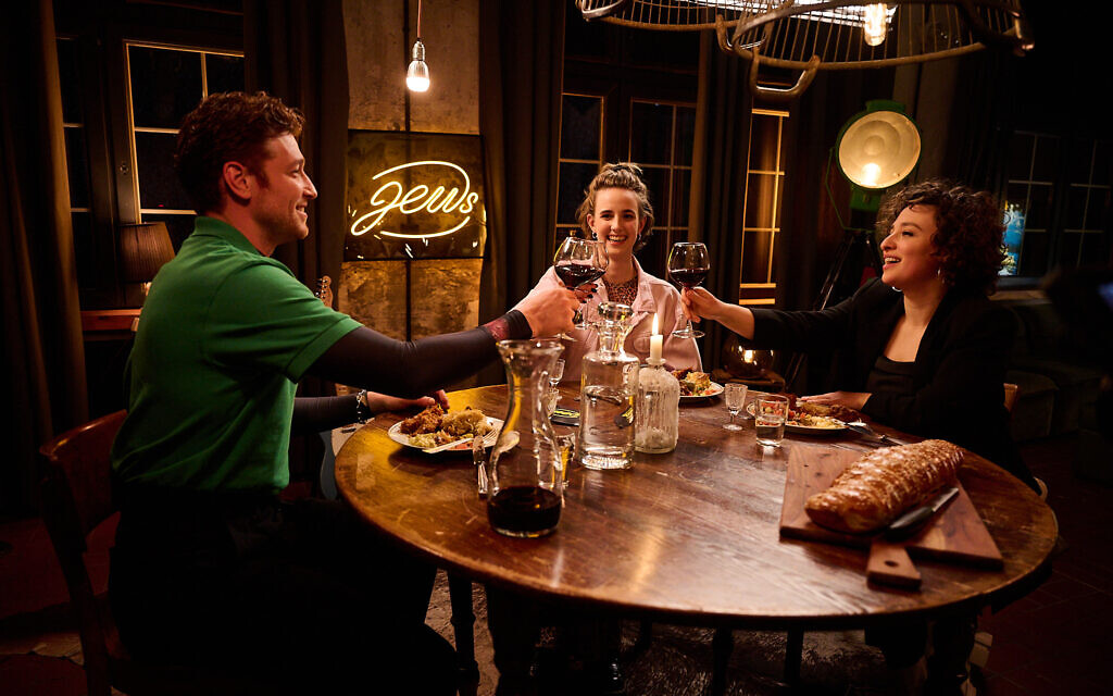 Actor Daniel Donskoy makes a toast with guests Helene Shani Braun, center, and Laura Cazes on Germany's 'Friday Night Jews.' (Christian Pries/JTA)