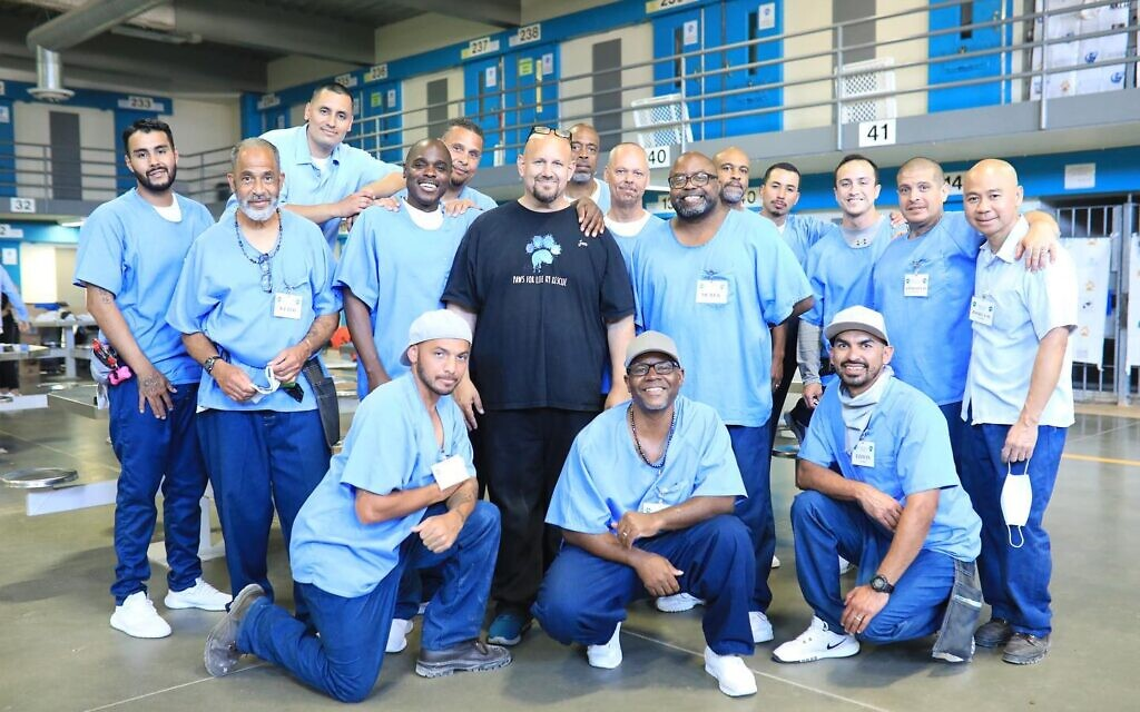 Jon Grobman (center) poses with a group of incarcerated men at California State Prison, Los Angeles County, in Lancaster. His own prison term behind him, Grobman now works as director of programs for Paws for Life K9 Rescue, which has incarcerated men train shelter dogs. (Courtesy of Rita Earl Blackwell, via JTA)