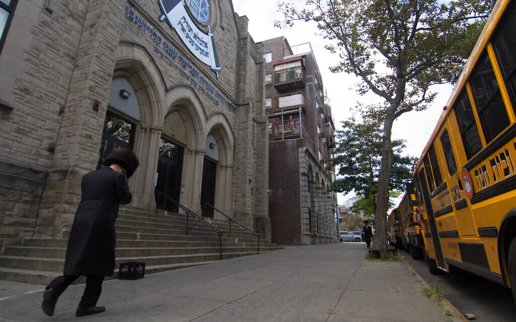 A man walks past an Orthodox yeshiva in Brooklyn, Sept. 29, 2020. (Daniel Moritz-Rabson/ via JTA)