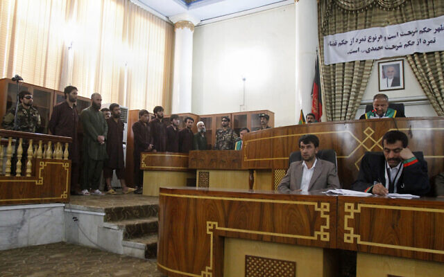 """Defendants attend a trial at the Primary Court in Kabul, Afghanistan, on May 6, 2015. The sign in Dari behind the judges reads, """"verdicts are based on Sharia (law), any rebellion against the verdict is rebellion against (the Prophet) Muhammad."""" (AP/Allauddin Khan)"""